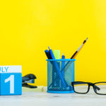79930546 - july 1st. image of july 1, calendar on yellow background with office supplies. summer time