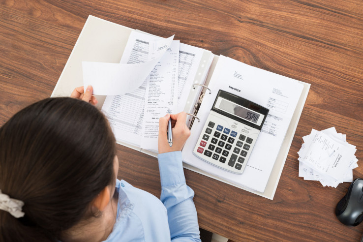39435815 - businesswoman calculating tax at desk with calculator in office